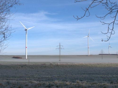 Eine Landschaftsaufnahme im Winter, man sieht 3 Windkraftanlagen und davor eine Freileitung.