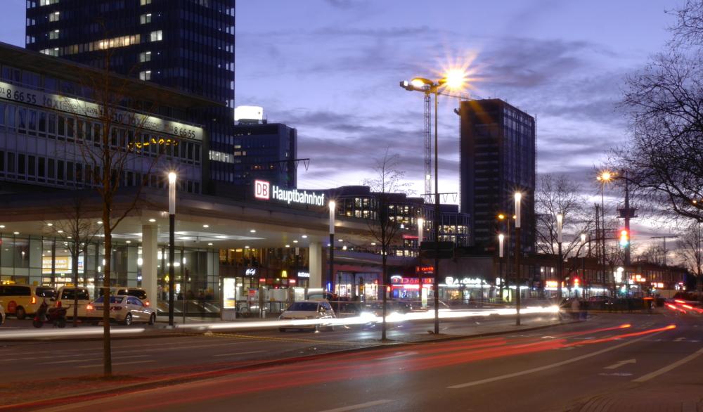 Das Foto zeigt den Eingangsbereich vom Hauptbahnhof in Essen während der Dämmerung. Von den Autos sieht man schon Lichtstreifen.