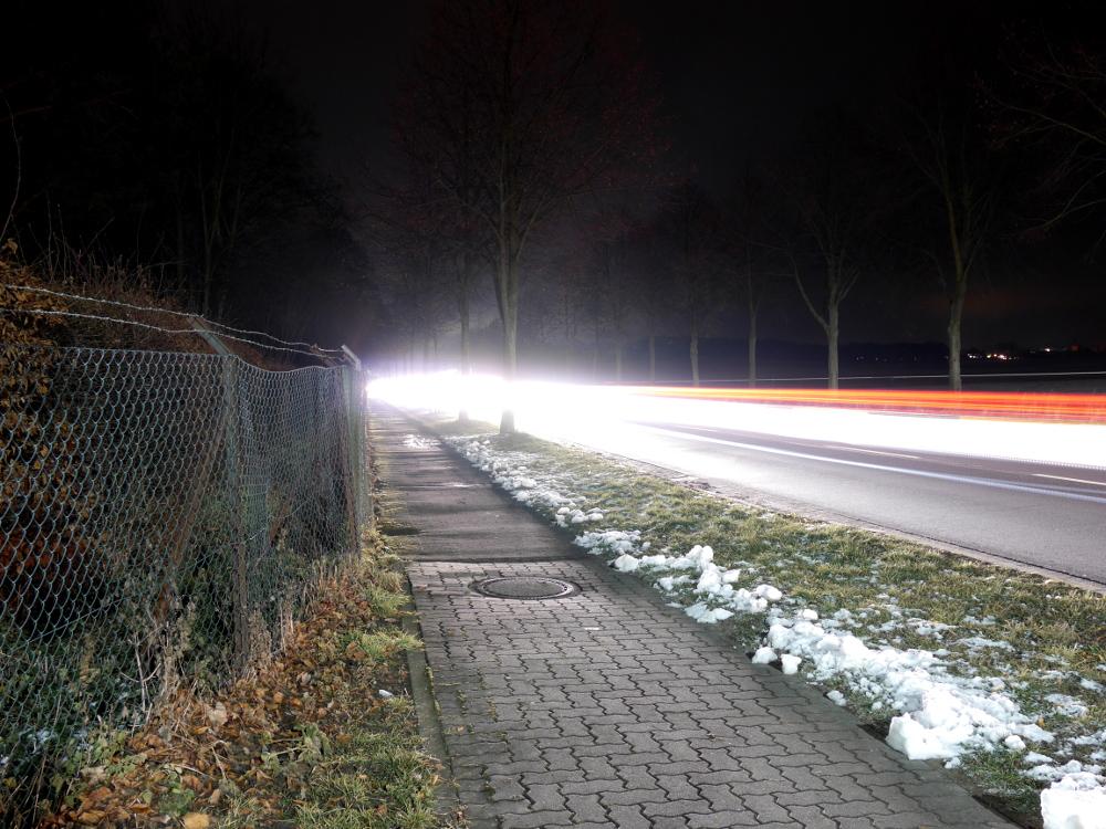 Das Foto zeigt eine nächstliche Straßenszene einer dicht befahrenen Durchgangsstraße, aur der linken Seite ist ein Fußweg, daneben die Straße mit Bäumen und den Lichtspuren von vielen Autos