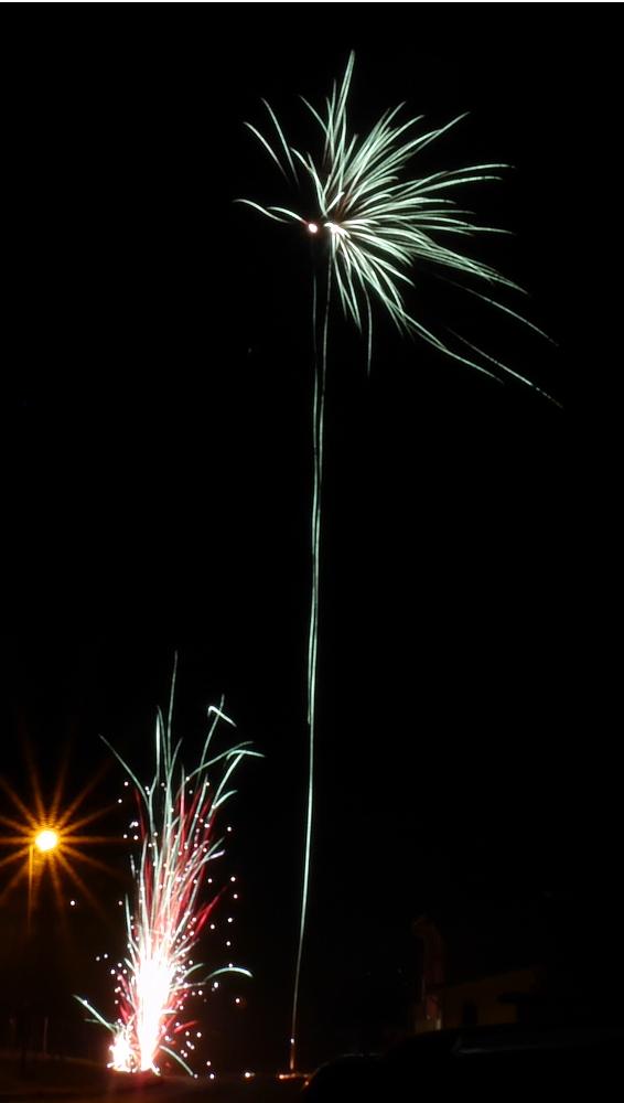Das Foto zeigt rechts eine Feuerwerksrakete und links ein Bodenfeuerwerk