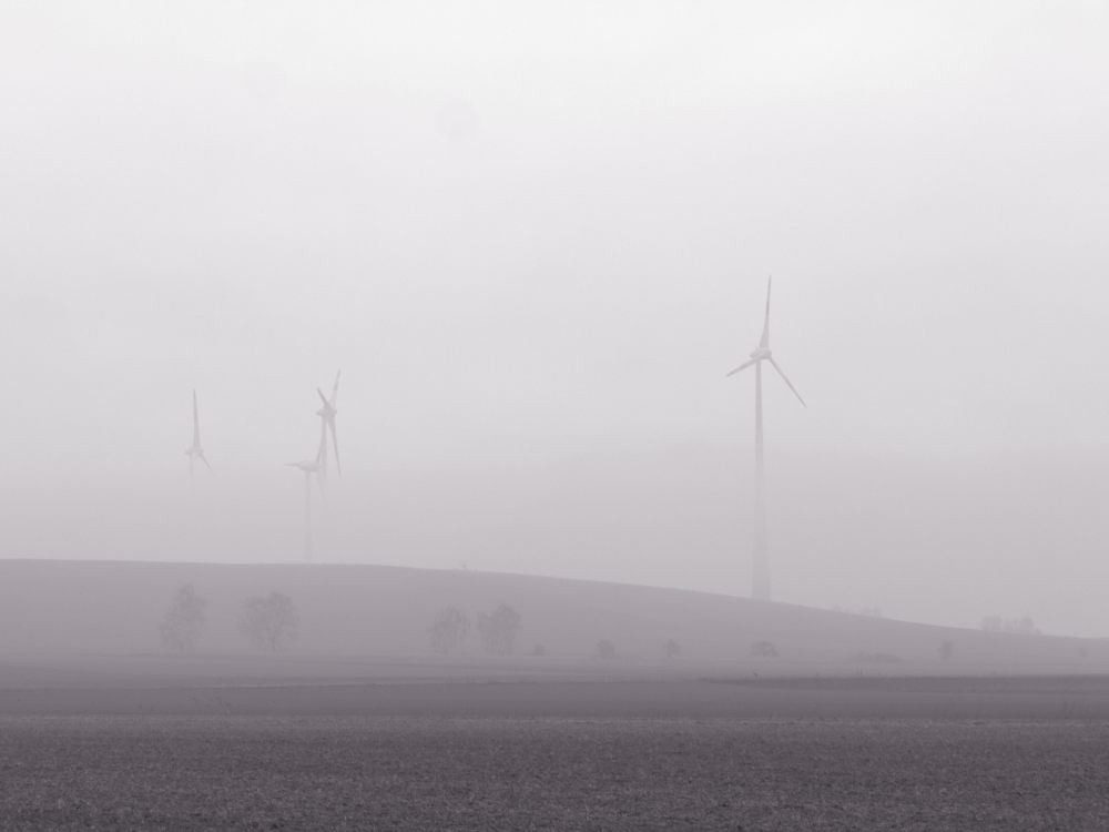 Das s/w-Foto zeigt eine Landschaftsaufnaume im Nebel, über dem Nebel sieht man die Köpfe von Windkraftanlagen