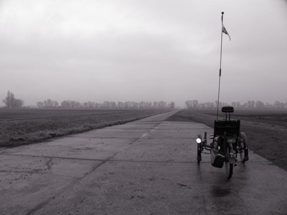 Das Foto zeigt einen Feldweg bei Nebel, hinten kann man noch Baumreihen erkennen. Auf einer Wegverbreiterung auf der rechten Seite steht ein Liegefahrrad.