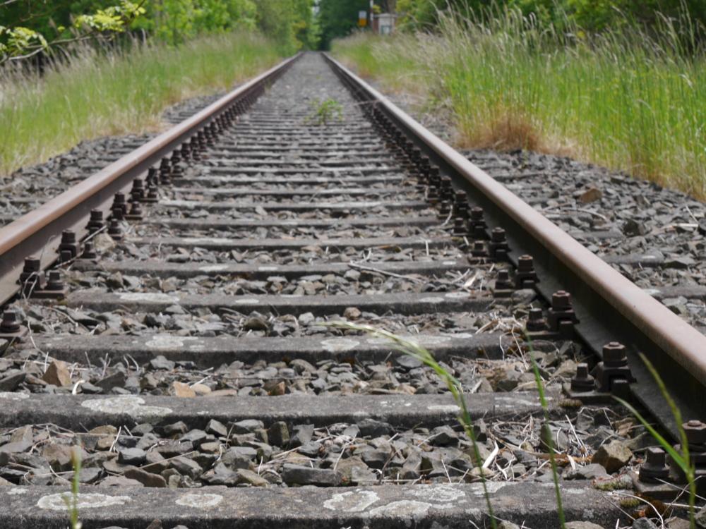 Das Foto zeigt ein Eisenbahngleis mit rostigen, lange nicht mehr befahrenen Schienen. Das Foto ist in Bodennähe aufgenommen und die Schienen führen in den Horizont