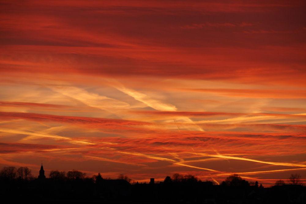 Farbfoto von einem Sonnenuntergang. Unten sind die Häuser von Roklum als Silouette, oben der Himmel kurz nach Sonnenuntergang, die Wolken sind in leuchtenden Roten, Orangenen und Gelben Farben. Man sieht auch leuchtende Kondensstreifen.
