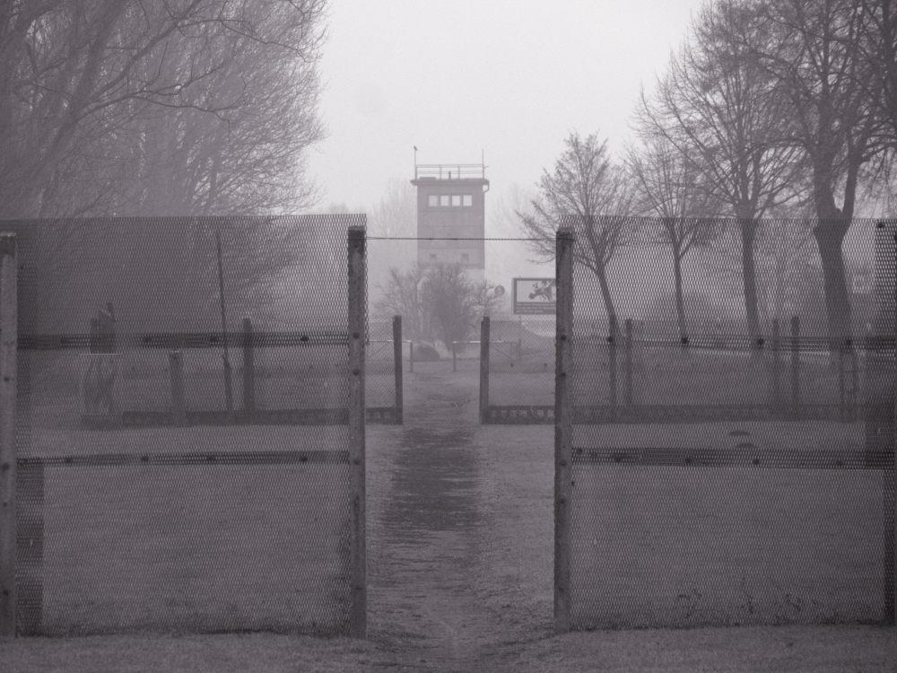 Das s/w-Foto zeigt einen Blick durch den Fußweg durch die nachgebaute Grenze auf den alten Grenzturm