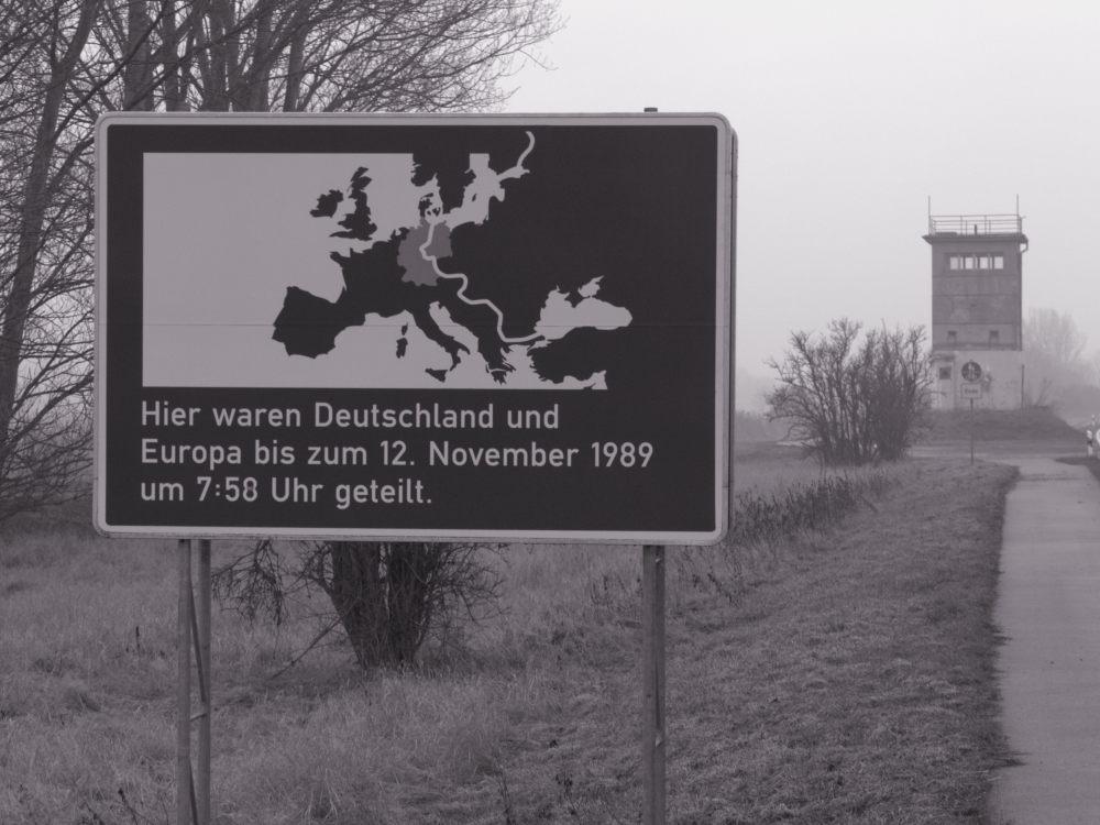 """Das Gedenk-Straßenschild das an dieser Stelle """"Deutschland und Europa bis zum 12.11.1989 um 7:58 Uhr geteilt"""" waren. Im Hintergrund der ehem. Grenzturm"""