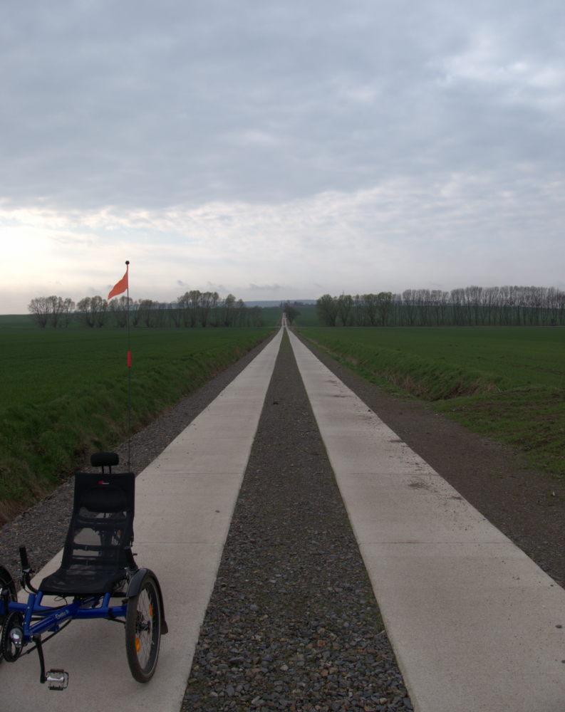 Das Foto zeigt einen langen Feldweg, der einen Berg hinunter geht. Der Feldweg besteht aus zwei Streifen aus Betonplatten, die gut erkennbar ist, dazwischen ist schwarzer Schotter. Am linken, unteren Bildrand sieht man teile eines blauen LIegefahrrads.