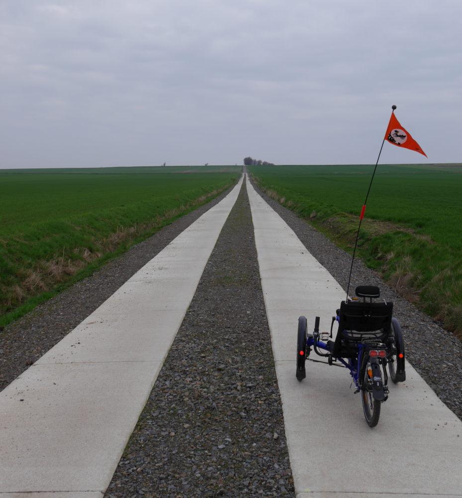 Das Foto zeigt einen Feldweg der einen Berg hinauf führt, er besteht aus 2 Streifen aus Betonplatten. Auf dem Gipfel des Berges stehen ein paar Bäume und rechts am unteren Rand steht ein Liegedreirad.