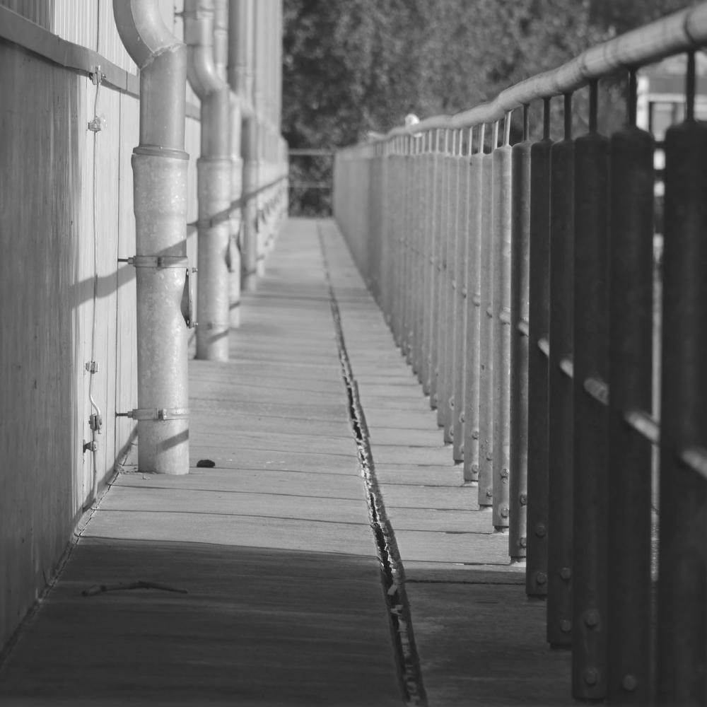 Das s/w-Foto zeigt einen Gang, rechts ist ein Metall-Gitterzaun, lins eine Betonmauer an der in regelmässigen Abständen Regenwasser-Fallrohre verlaufen. Die Sonne erzeugt durch den Gitterzaun ein Muster auf dem Betonboden des Gangs