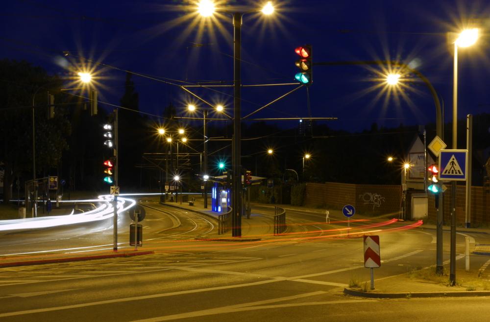 Das Foto zeigt eine nächtliche Straßenszene mit Straßenbahnhaltestelle und Ampeln. Von den Vorder- und Rücklichtern der Autos sieht man nur noch Streifen und alle Ampeln leuchten gleichzeitig...