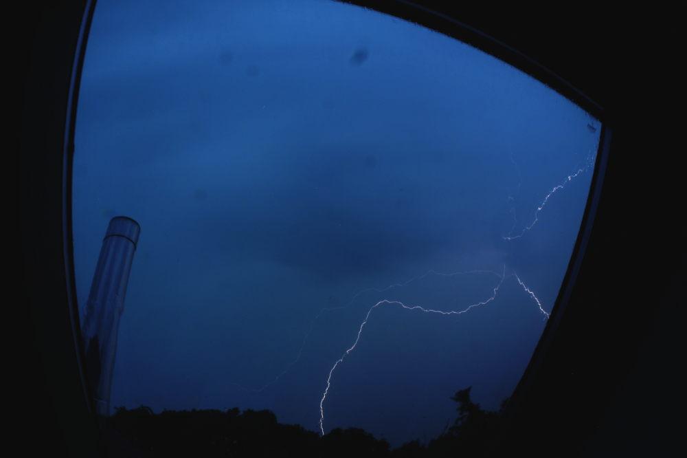 Das Foto zeigt die Blitze eines Gewittters durch ein Dachfenster, es sieht so aus, als würden sich die Blitze alle an einer Stelle treffen.