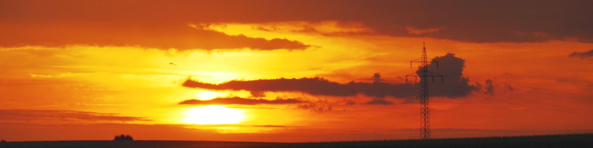 Das Foto zeigt einen Sonnenuntergang, die Sonne ist teilweise von Wolken verdeckt und berührt fast den Horizont. Im rechten Drittel des Bildes kann man einen Hochspannungsmast sehen