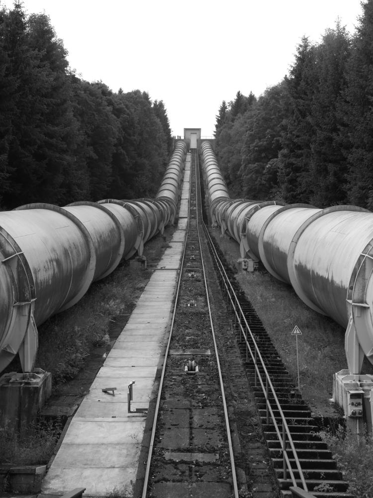 """Das s/w-Foto zeigt die beiden Rohre des Pumpspeicherkraftwerks von """"unten"""", man sieht also in Richtung des Maschinenhauses am oberen See."""