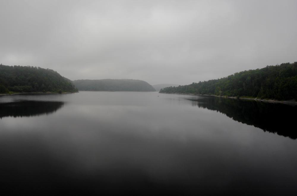 Das Foto zeigt den See einer Talsperre im Harz bei Nebel, es ist sehr Grau. Zu beiden Seiten des Sees und am Ende sieht man bewaldete Berge.