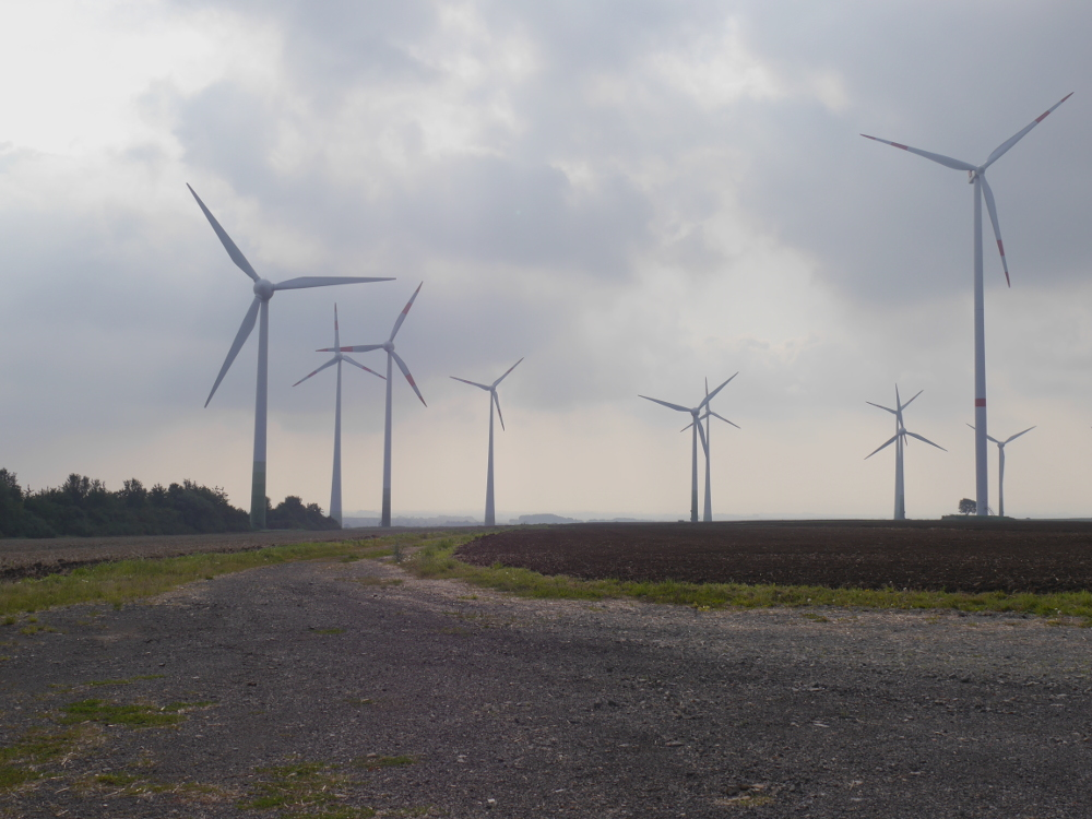 Das Foto zeigt 10 Windkraftanlagen vor grauem Himmel