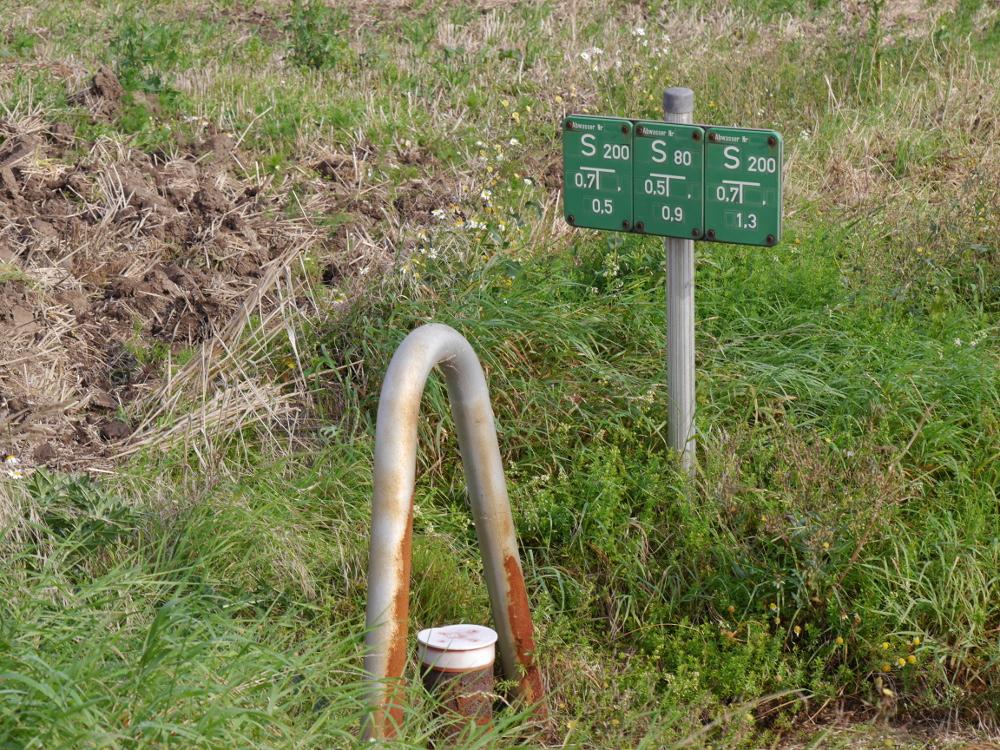 Das Foto zeigt drei Grüne Schmutzwasser-Hinweisschilder, davor ein Rohr mit einem Schutzbügel drüber.
