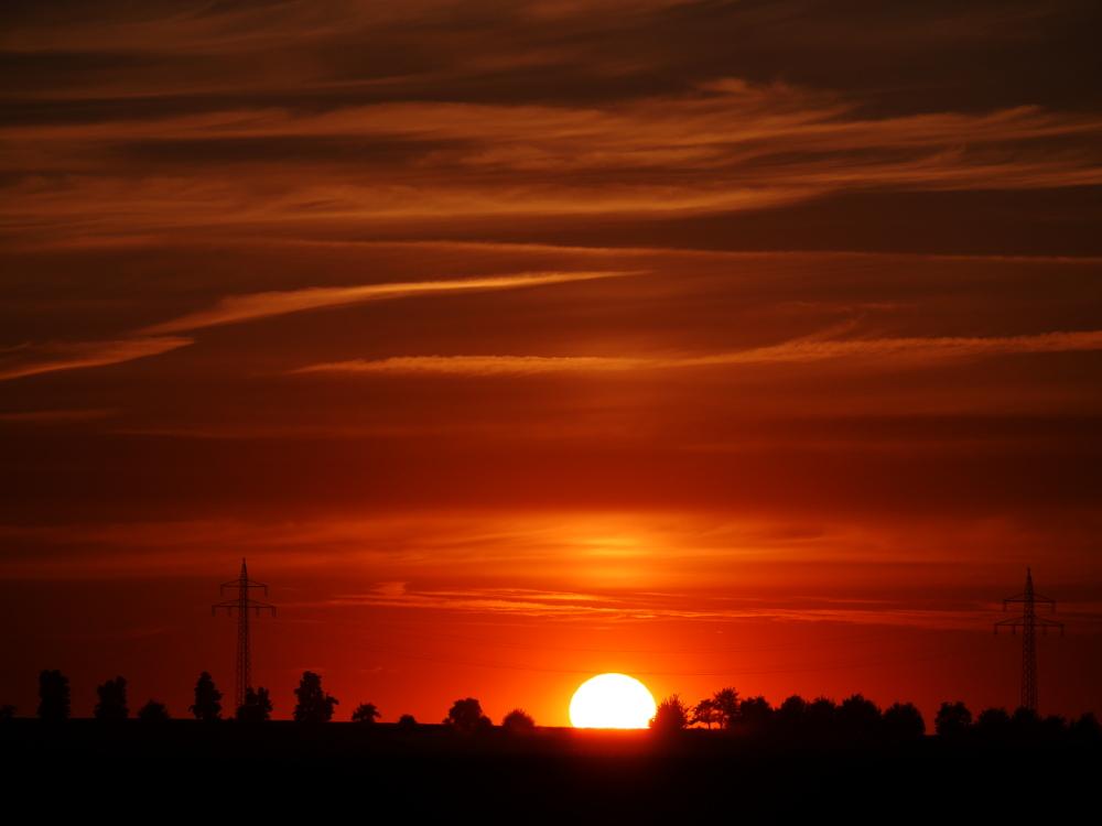 """Ein Sonnenuntergang als Landschaftsbild. Die Sonne ist schon teilweise """"versunken"""", Rechts und Links der Sonne stehen die Masten einer Hochspannungs-Freileitung"""