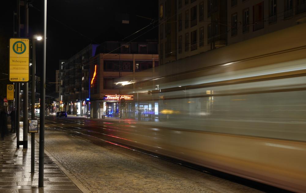"""Das Foto zeigt die Straßenbahn-Haltestelle Webergasse bei Nacht. Etwa in der linken Bildhälfte sieht man die """"Spuren"""" einer ausfahrenden, gelben Straßenbahn."""