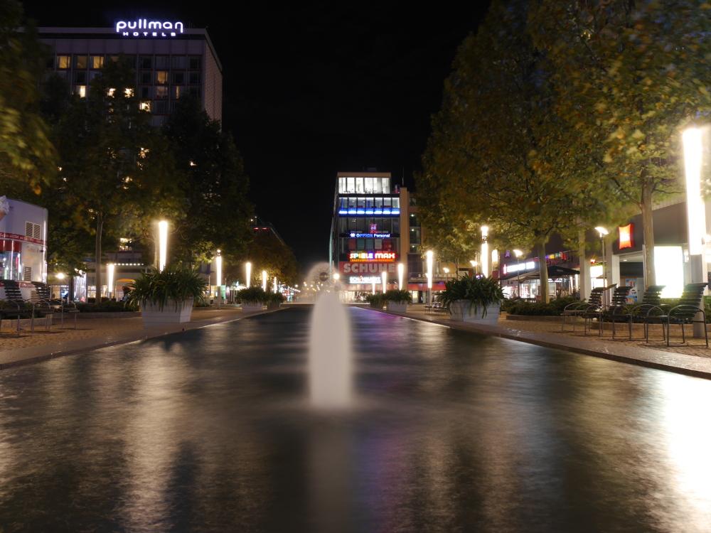 """Das Foto zeigt eine Nachtaufnahme von Springbrunnen in der Dresdner Innenstadt, man sieht erst eine """"Normale"""" Wasserfontäne, dann eine Art Wasser-Pustblume. Rund herum sind erleuchtete Geschäfte"""