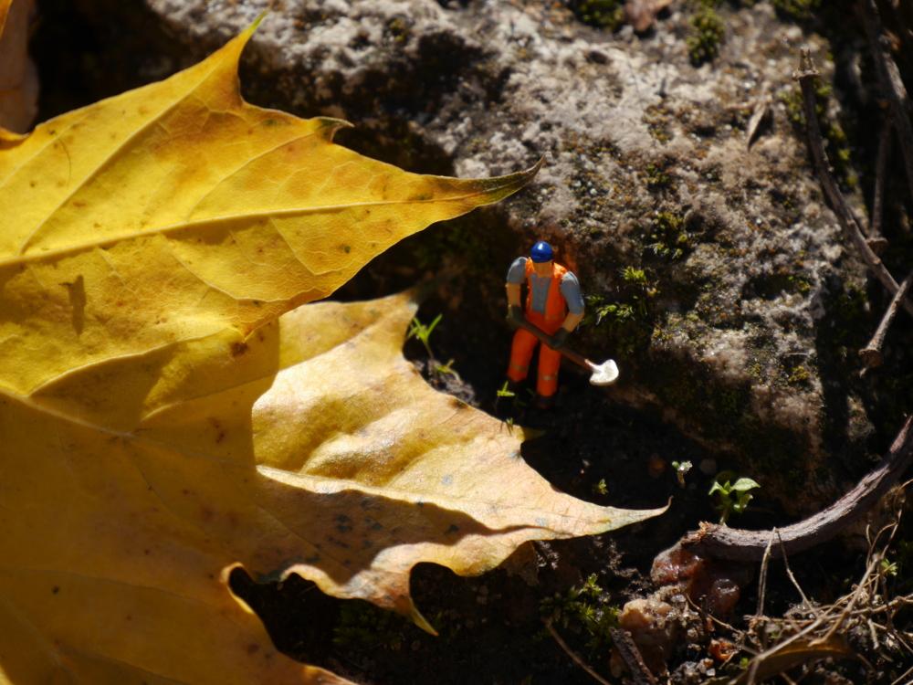 Das Foto zeigt einen Modelleisenbahn-Bauarbeiter mit Schaufel an einem gelben Blatt.