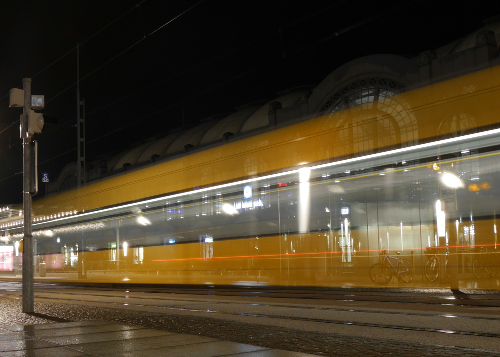 Das Foto ist eine Langzeitbelichtung am Dresdner hauptbahnhof. Man sieht eine Straßenbahn durchs Bild fahren, durch die Gelbe Bahn scheint der Hauptbahnhfo durch.