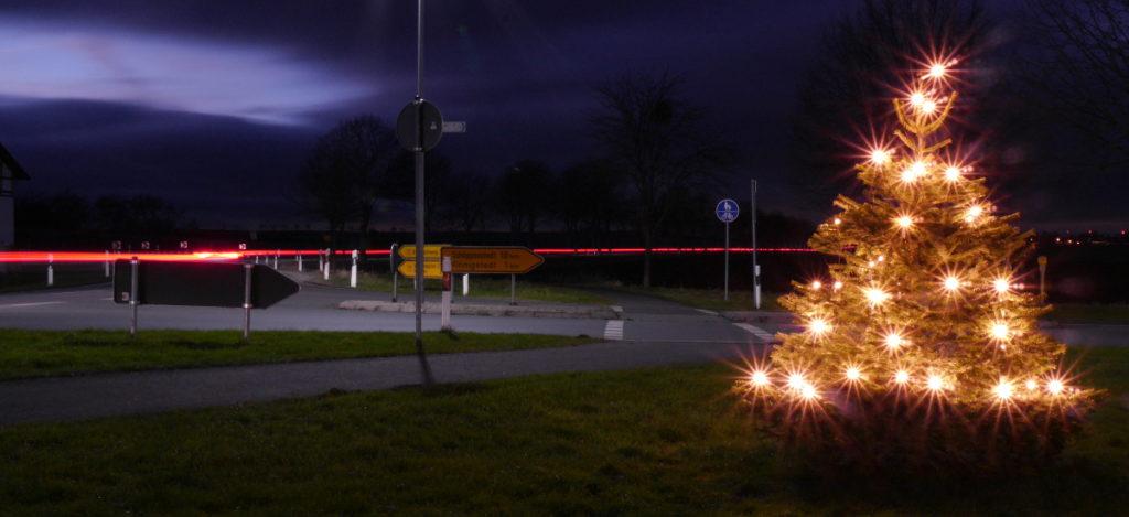 Das Foto zeigt eine Nachtaufnahme von einem beleuchteten Weihnachtsbaum an einer Einmündung, der Baum steht in der rechten Bildhälfte. Auf der durchgehenden Straße sieht man die roten Spuren der Rücklichter von Autos