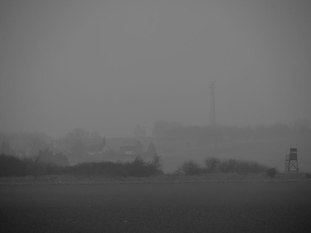 Das s/w-Foto zeigt eine Landschaftsaufnahme bei leichtem Nebel. Recht gut ist auf der rechten Seite ein Hochsitz zu erkennen, weiter hinten die Häuser eines Dorfes und ganz hinten ein Matallgitter-Mast für Mobilfunk.