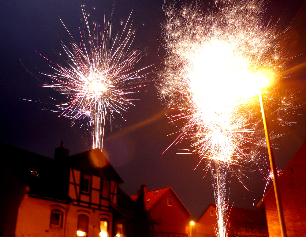 Das Foto zeigt Feuerwerk über den Häusern.