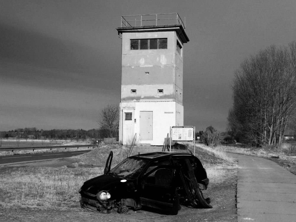 Das s/w-Foto zeigt ein ausgeschlachtetes, vandaliertes Auto vor dem Grenzturm in Mattierzoll