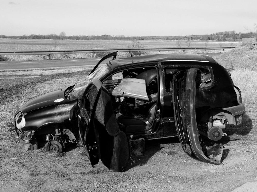 Erneut das ausgeschlachtete Auto, man sieht das im Fahrzeuginneren alle möglichen Teile des Autos rumfliegen und die Reifen abmontiert wurden.