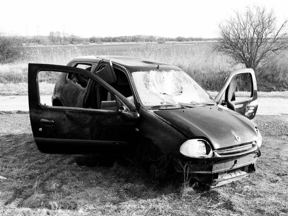Das Auto von Vorne, die Türen sind auf, die Scheiben aingeschlagen, die Frontscheibe gesplittert und die Leuchten zerstört.
