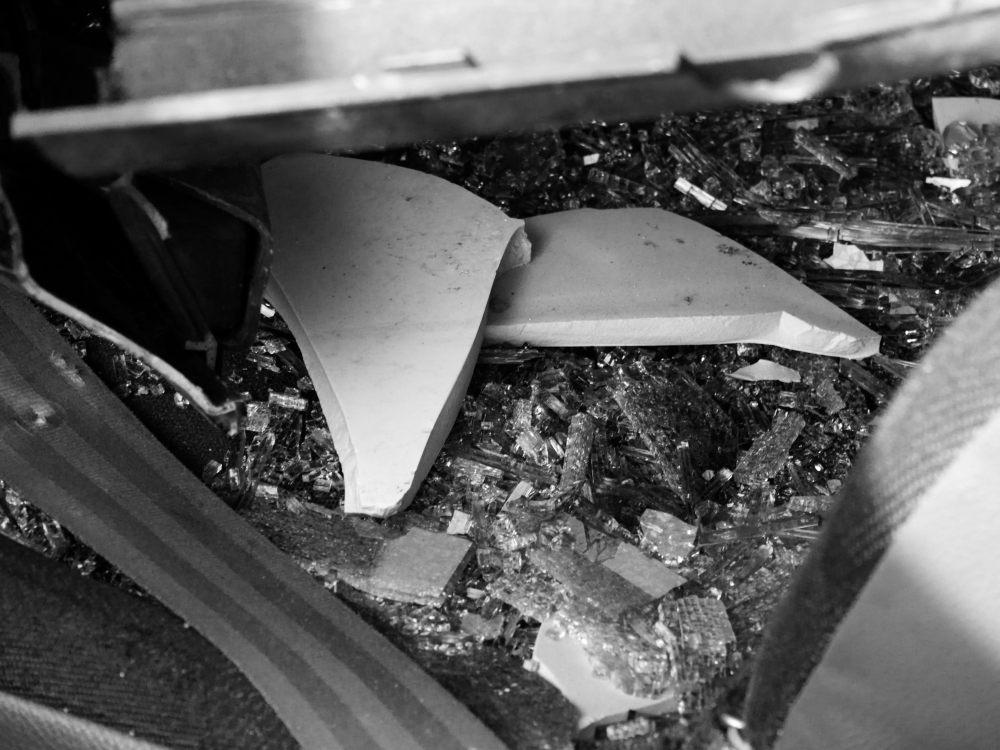 Detail aus dem Fußraum: Der Gurt, daneben Glassplitter und Keramiksplitter, die wohl nicht von dem Auto stammen.