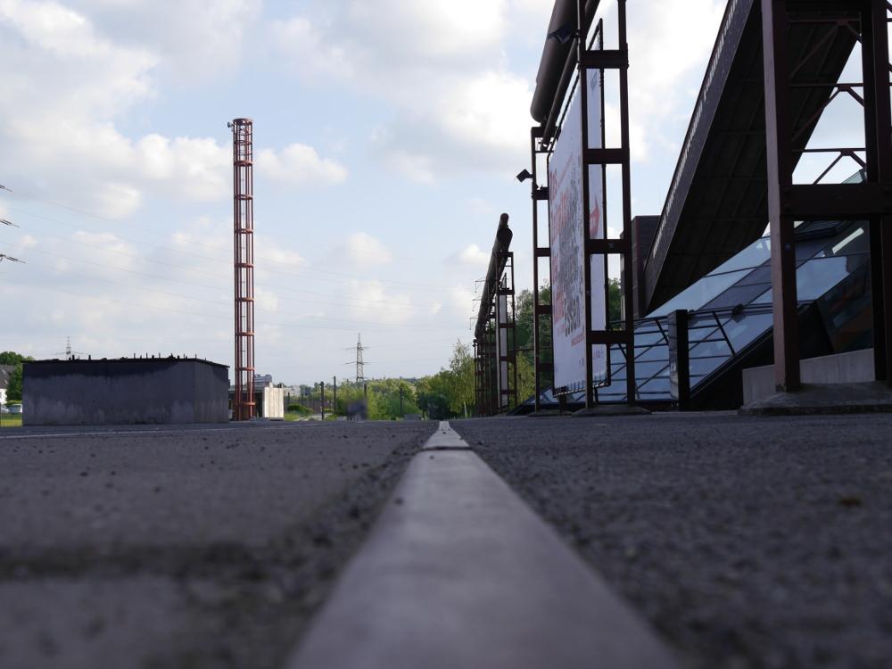 Dieses Foto ist entlang einer Schiene Fotografiert, links ist freie Fläche, rechts stehen große Plakate.