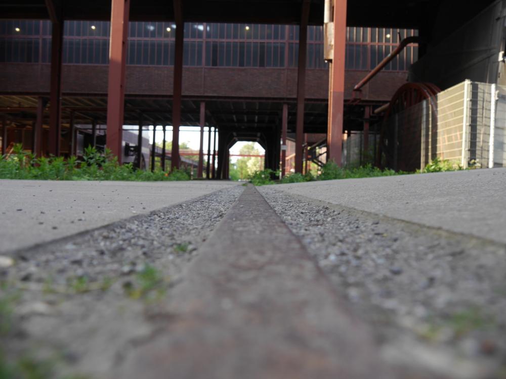 Das Foto ist entlang einer Schiene aufgebaut, man sieht die Reste einer Verladeanlage