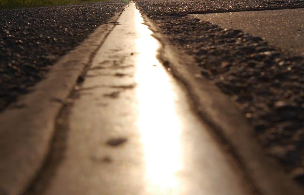 Das Foto ist der Blick entlang einer Schiene, man sieht die Sonne, welche sich in der Schiene spiegelt..