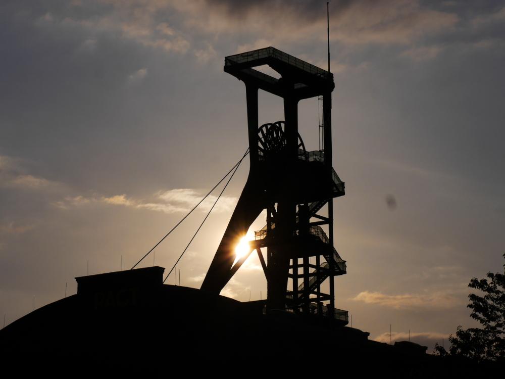 Das Foto zeigt einen Bergbau-Förderturm im gegenlicht der untergehenden Sonne