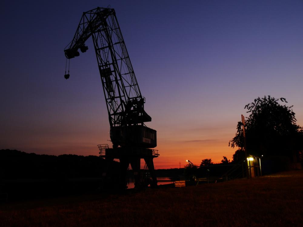 """Das Foto zeigt einen großen Hafenkran in der """"blauen Stunde"""" nach dem Sonnenuntergang, im Hintergrund sieht man noch einen Rest der Sonne in Orange leuchten"""