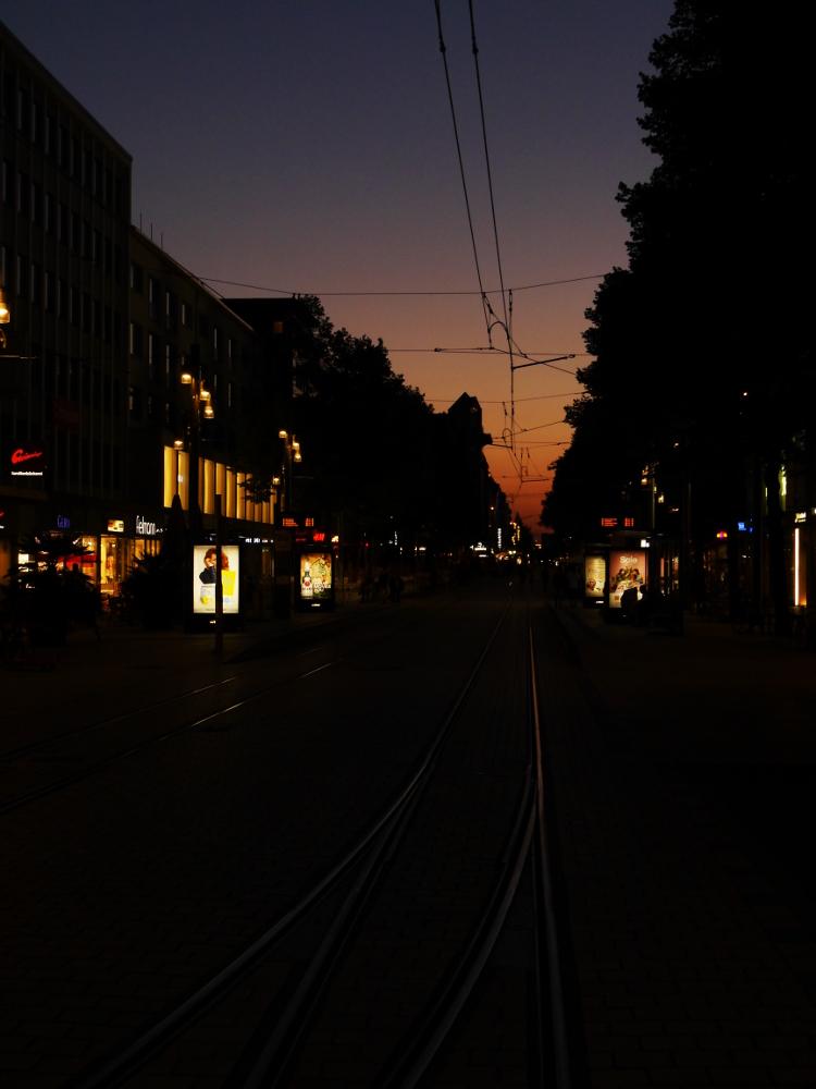 Das Foto ist eine Aufnahme am späten Abend nach Sonnenuntergang, man sieht im HIntergrund noch das letzte orangene Glühen, ansonsten aber nur das LIcht der Geschäfte und Werbetafeln. Mittig durch das Bild gehen Straßenbahnschienen