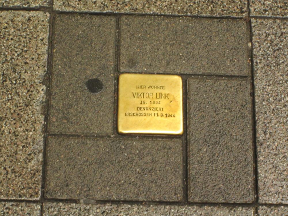 """Das Foto zeigt einen im Fußweg verlegten Stolperstein: """"Hier wohnte Viktor Link, Jg. 1894, Denunziert, Erschossen 11.9.1944"""""""