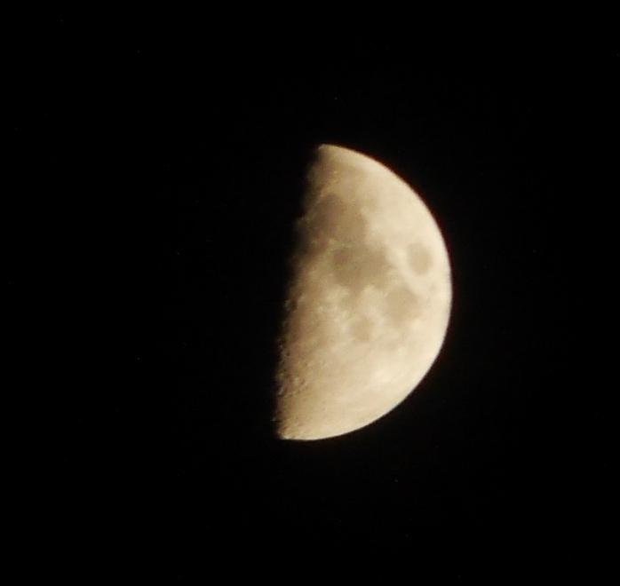 Das Foto zeigt den Mond, etwa bei Halbmond...