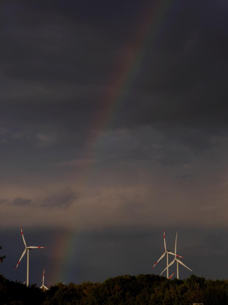 Das Foto zeigt einen Regenbogen am dunkelen Himmel, der Regenbogen beginnt am Boden bei Windkrafträdern