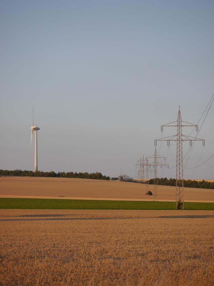 Das Bild zeigt auf der rechten Seite eine Hochspannungs-Freileitung, die über Felder führt. Links ist ein Windrad zu sehen und am Horizont in der Mitte eine kleine Umspannstation