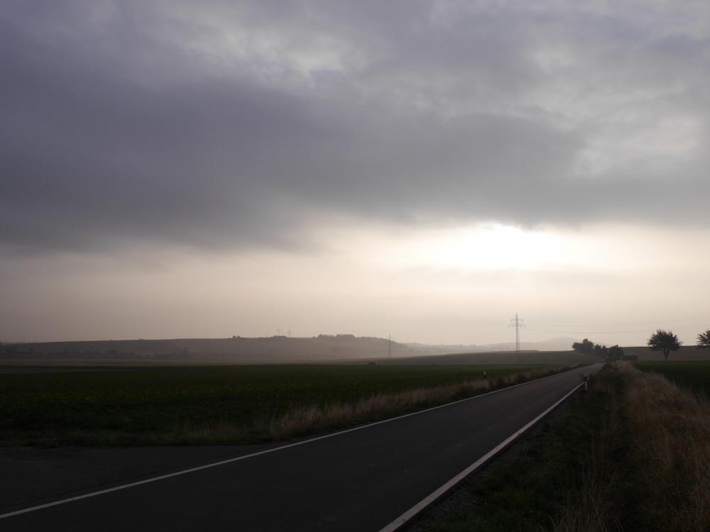 Eine Landschaftsaufnahme bei Wolen und leichtem Nebel, durch das Bild verläuft eine Straße