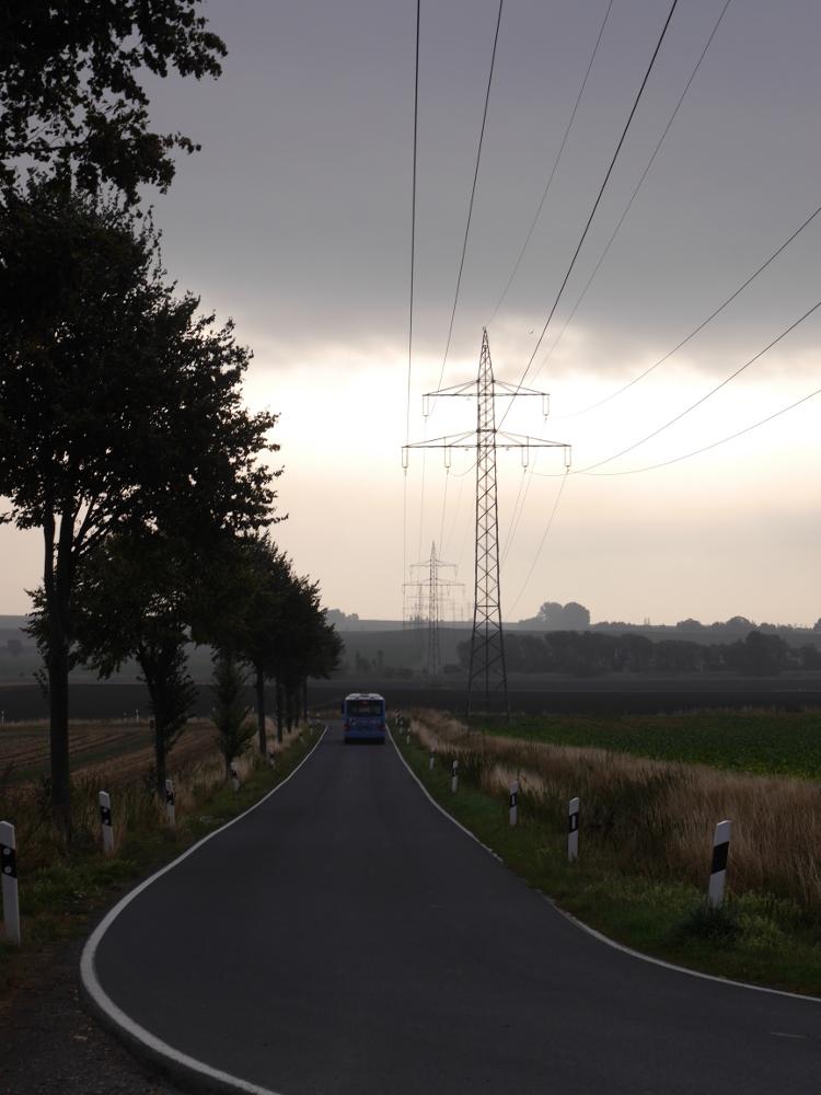 Landschaftsaufnahme bei Wolken und leichtem Nebel, man sieht eine gerade Freileitungstasse, parallel zur Trasse verläuft im ersten Teil eine Straße, auf der ein Bus fährt.