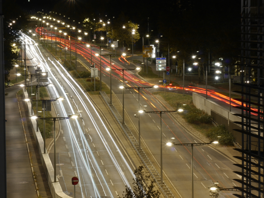 Das Foto zeigt die Langzeit-Aufnahme einer mehrspurigen Straße in Dresden. Aufgrund der langen Belichtungszeit sind die Lichter der Fahrzeuge nur Streifen.