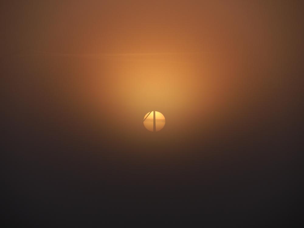 Dasa Foto zeigt einen Sonnenaufgang im Nebel, durch die Mitte der Sonne geht ein Windrad