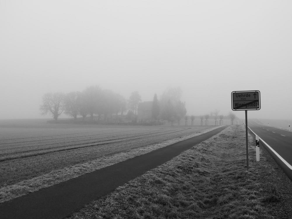 Das s/w-Foto zeigt den Friedhof von Winnigstedt im Nebel, auf der rechten Seite sieht man das Orts-Ausgangsschild von Winnigstedt in Richtung Uehrde.