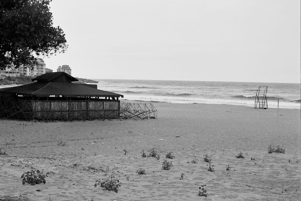 Das s/w-Foto zeigt den Strand von Sozopol zum Saisonende, der Verkaufsstand ist geschlossen und verramelt, der Rettungsschwimmer-Posten ist leer und am Strand sind keine Menschen zu sehen.