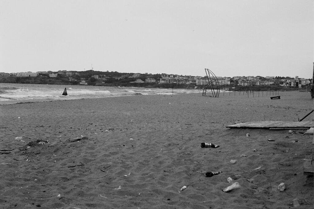 Das Foto zeigt den Strand von Sozopol, es sind keine Touris zu sehen, der Rettungsschwimmer-Turm ist leer, dafür liegt viel Müll rum. Ein einsamer Sonnenschirm ist zu sehen.