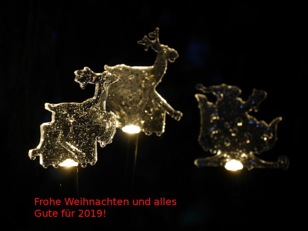 """Das Foto zeigt drei Plexiglas-Weihnachtsfiguren, welche von unten beleuchtet werden. Außerdem sind daran Regentropfen. Unter den Figuren steht """"Frohe Weihnachten und alles Gute für 2019!"""""""